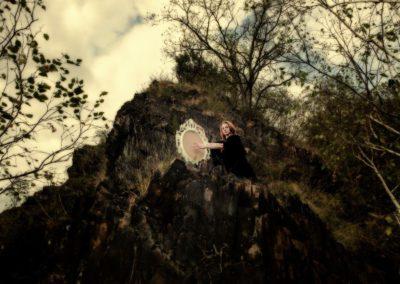Noira s magickým zrcadlem na skále nad řekou
