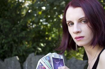 věštkyně Noira s vykládacími kartami v rukou venku v přírodě