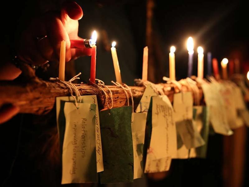Svíčky hoří nad visačkami s přáními, příklad moderního magického rituálu